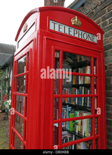 An old red British Telephone box turned into a British village eccentric lending library - Stock Image