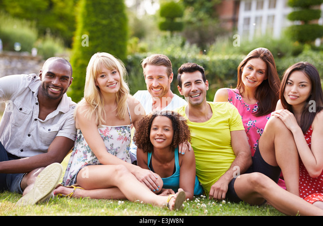 Group Of Friends Sitting On Grass Together - Stock Image
