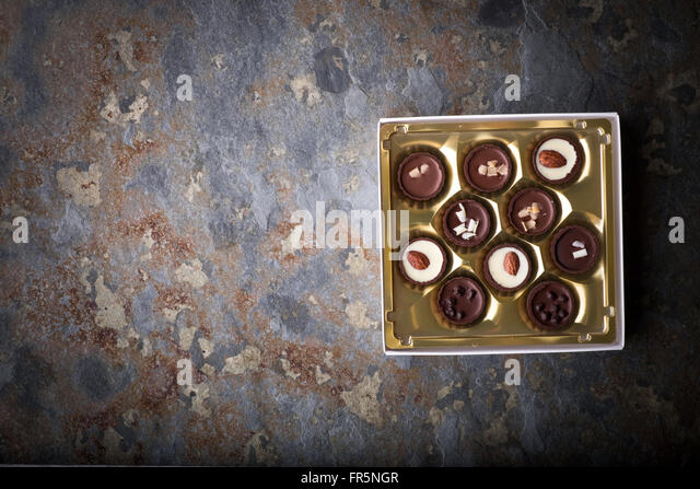 Set of chocolate candies on a blue stone horizontal - Stock Image