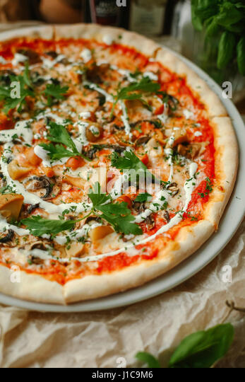 Gourmet pizza with basil on plate - Stock Image