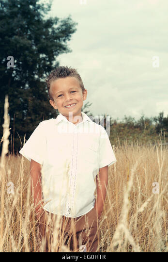 Portrait of boy amongst wild grasses - Stock Image