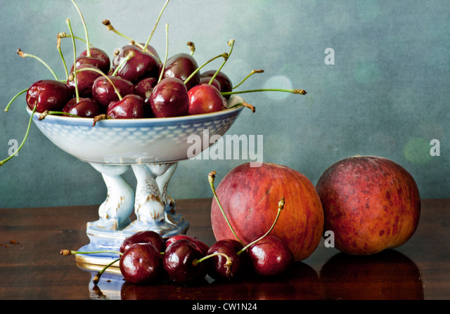 Interior with dark red cherries on a china tray and peaches on a wooden polished table - Stock-Bilder