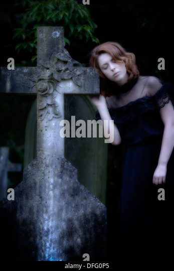 a girl in a black dress on a graveyard - Stock Image