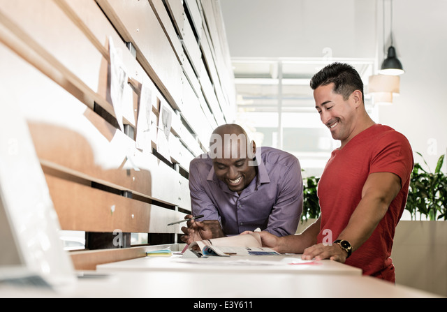 Two male business colleagues sharing a laugh in office - Stock Image