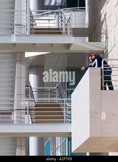 A man and a woman on a balcony next to a staircase at the J. Paul Getty Center in Los Angeles, CA. - Stock Image