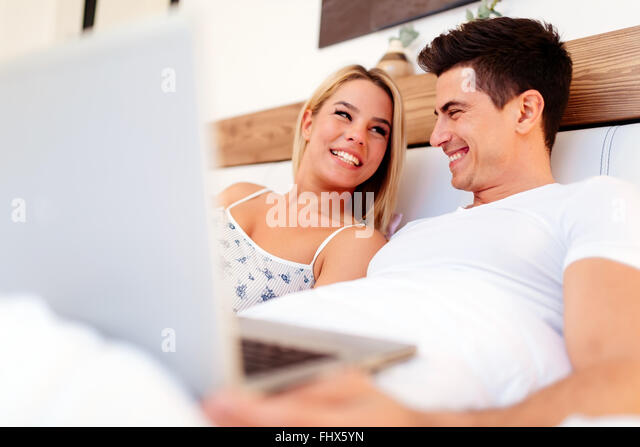 Beautiful couple using laptop in bed while being truly happy - Stock Image