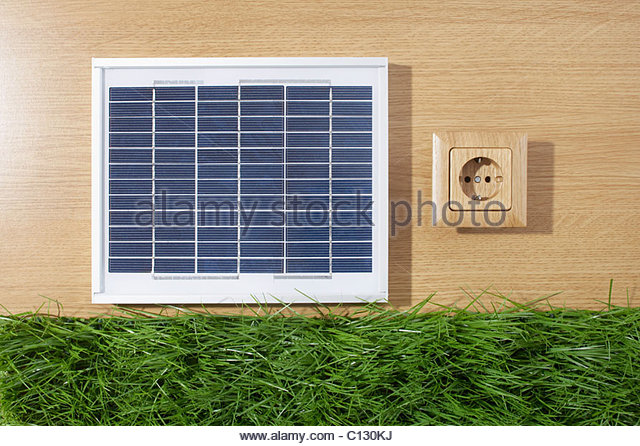 still life of solar panel wooden power socket and grass - Stock Image