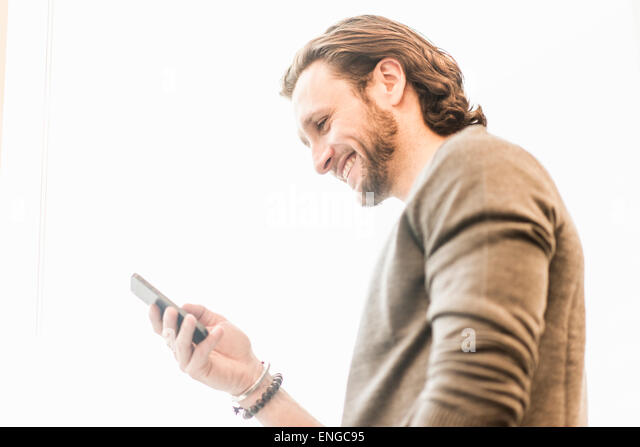 A bearded man smiling and checking his phone. - Stock Image