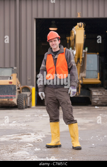Transportation engineer standing at heavy construction equipment garage - Stock Image
