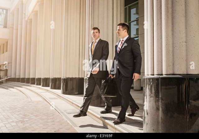 Two business lawyers with briefcase leaving courthouse - Stock-Bilder