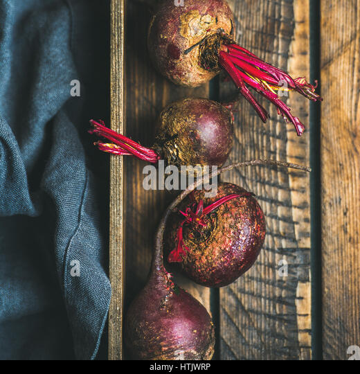 Raw organic purple beetroots in wooden box, square crop - Stock Image