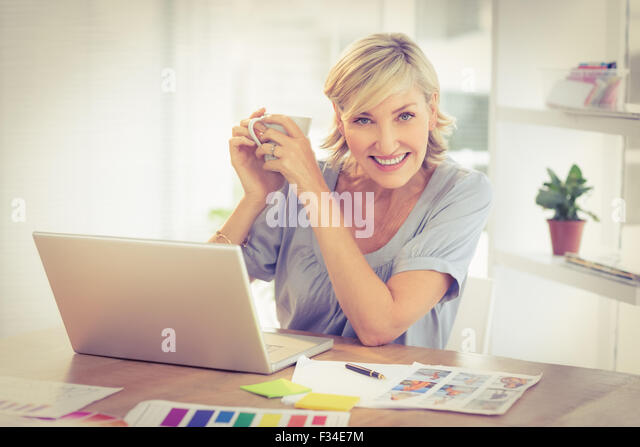 Smiling businesswoman working on a laptop - Stock-Bilder