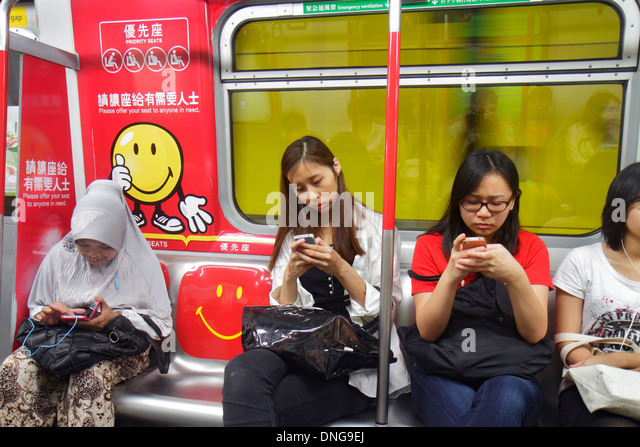 Hong Kong China Island Wan Chai MTR Subway Station public transportation riders passengers Asian woman smartphone - Stock Image