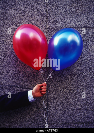 A man holding red and blue balloons - Stock Image