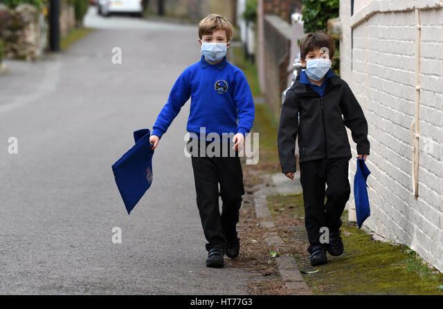 Children walking to school wearing smog pollution masks Britain Uk - Stock Image