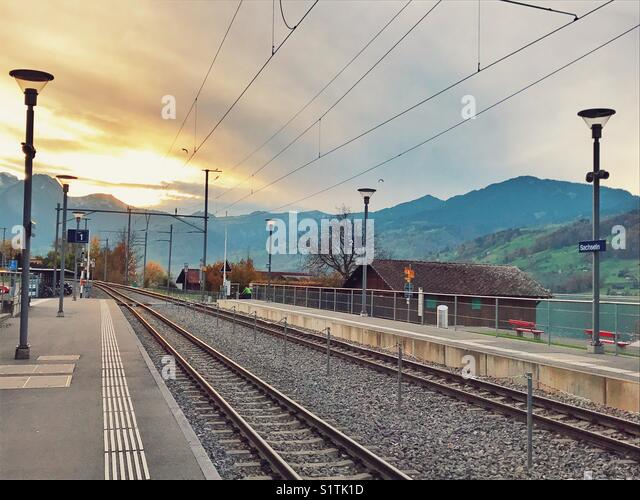 Railway track at sunset in Switzerland - Stock Image
