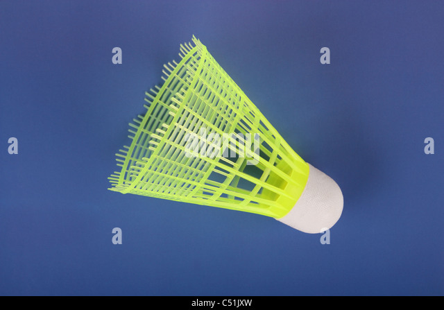 One yellow badminton shuttlecock on a dark blue background - Stock Image