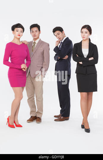 Contrasting business people in retro styles and black suits standing staring at front - Stock Image
