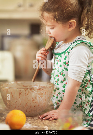 Child tasting cake mix with wooden spoon - Stock-Bilder