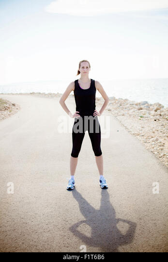 Young woman in sports clothing outdoors - Stock Image