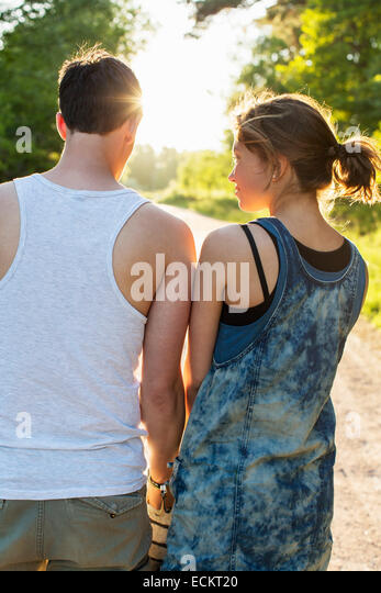 Rear view of couple standing against bright sun - Stock Image
