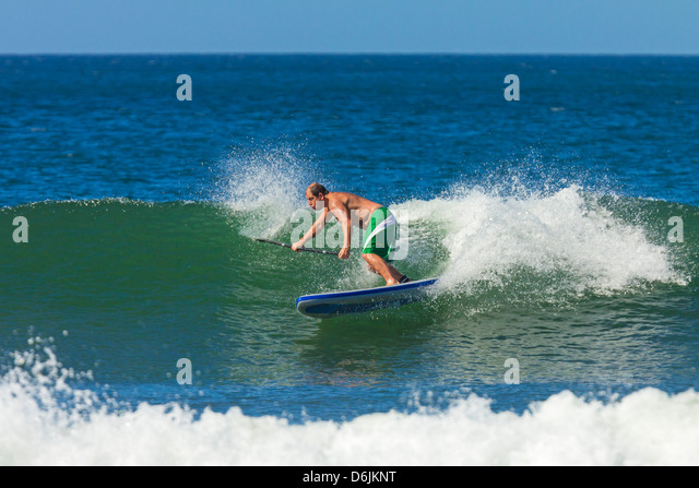 Man surfing inflatable paddle board at Playa Guiones beach, Nosara, Nicoya Peninsula, Guanacaste Province, Costa - Stock Image