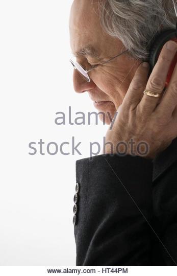 Close up senior man listening to music with headphones against white background - Stock-Bilder