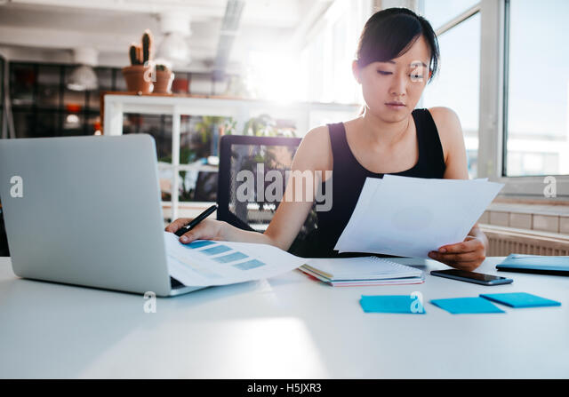 Portrait of young asian woman reading documents at her desk. Businesswoman at her workplace doing paperwork. - Stock Image