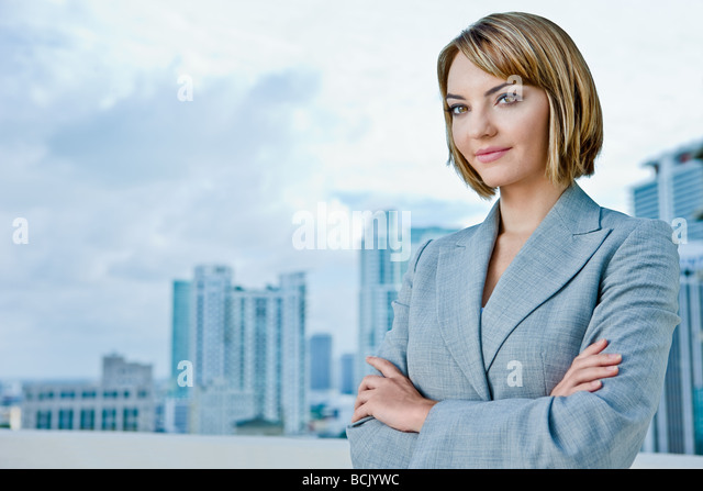 Attractive young business woman looking into camera see other file looking into distance - Stock Image