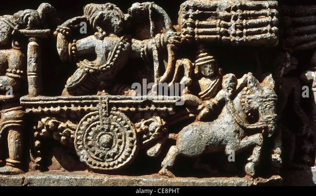 MAA 81242 : mahabharat sculpture Arjuna with bow and arrow in chariot in hoysalaswara temple halebid karnataka india - Stock Image