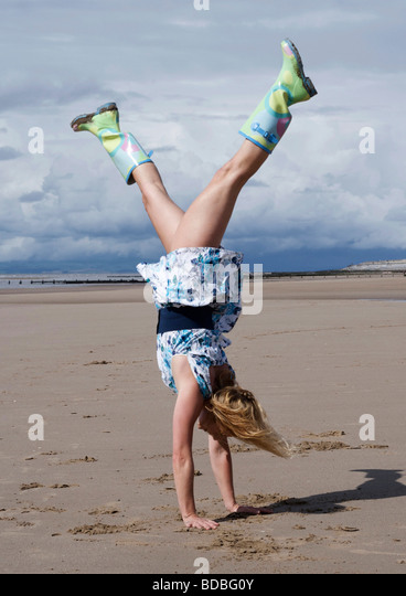 woman wearing an old-fashioned floral dress and wellington boots, doing a handstand on the beach - Stock-Bilder