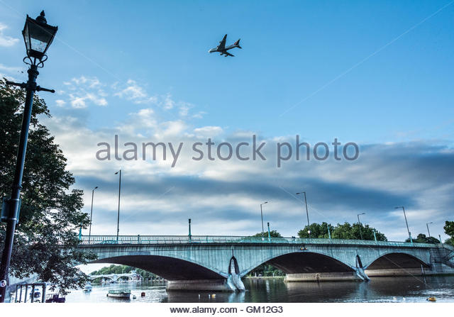 A plane comes in to land at Heathrow passing Twickenham Bridge on the river Thames in London, UK - Stock Image