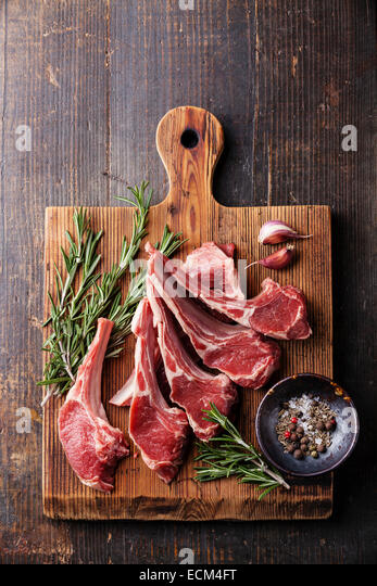 Raw fresh Lamb Meat ribs and seasonings on dark wooden background - Stock Image