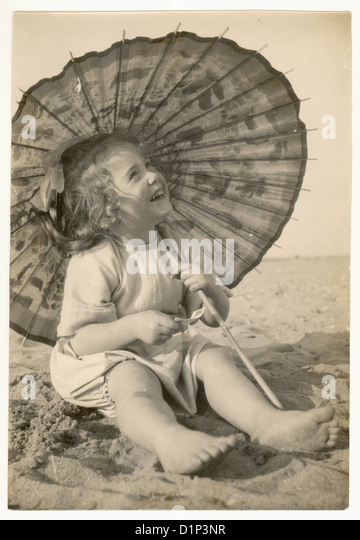 Photograph of cute young girl on a beach, holding a parasol, 1930's - Stock Image