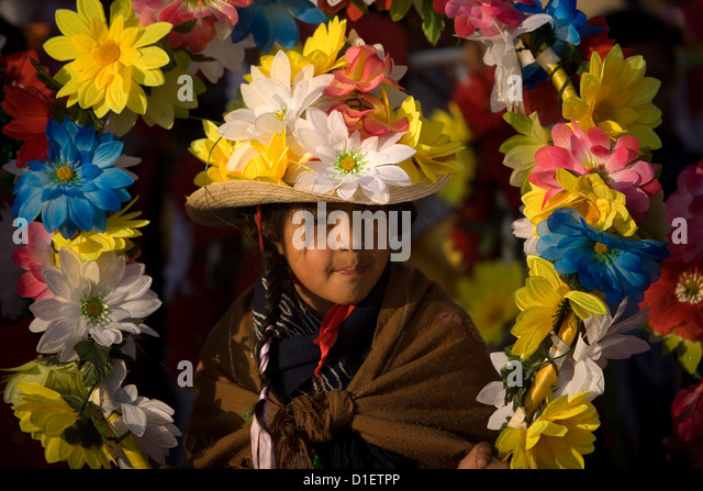 An indigenous Mazahua girl carries flowers outside of the Our Lady of Guadalupe Basilica in Mexico City, December - Stock Image