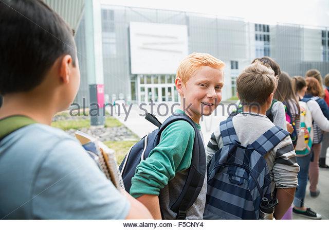 Portrait smiling schoolboy arriving science center with classmates - Stock Image