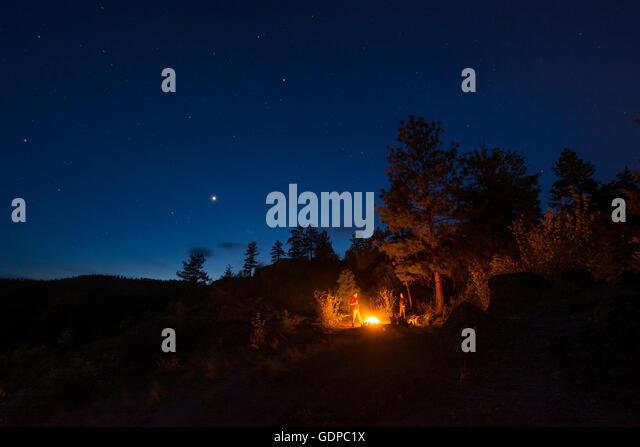 Friends round campfire, Pincushion Mountain, Peachland, British Columbia, Canada - Stock Image