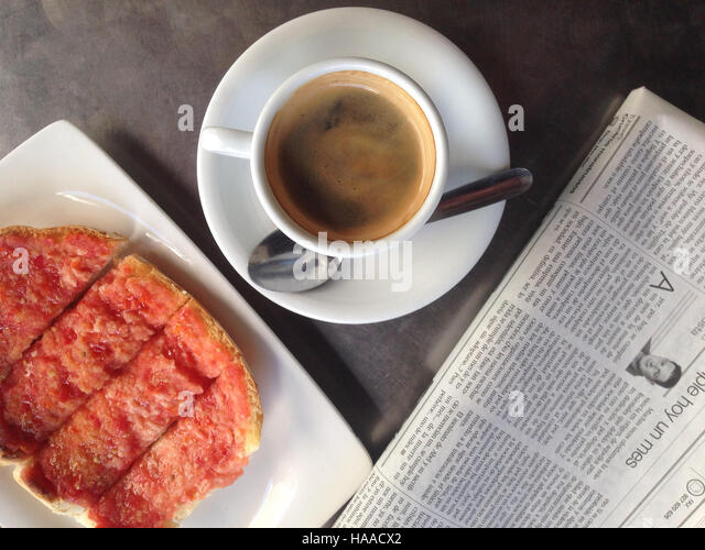Badajoz, Spain - 21 May 2016: fresh tomato toast and black coffee on the breakfast table with a newspaper - Stock Image