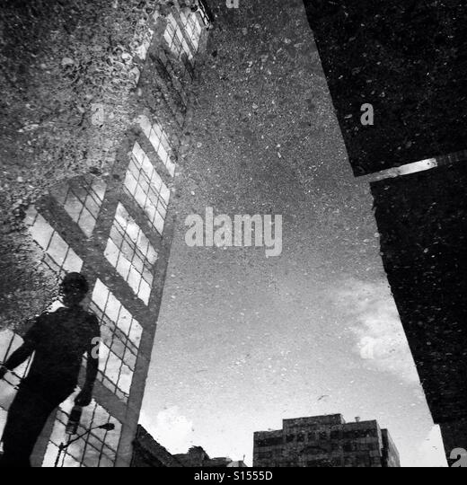 A person and a building are reflected in a puddle in an urban setting - Stock-Bilder