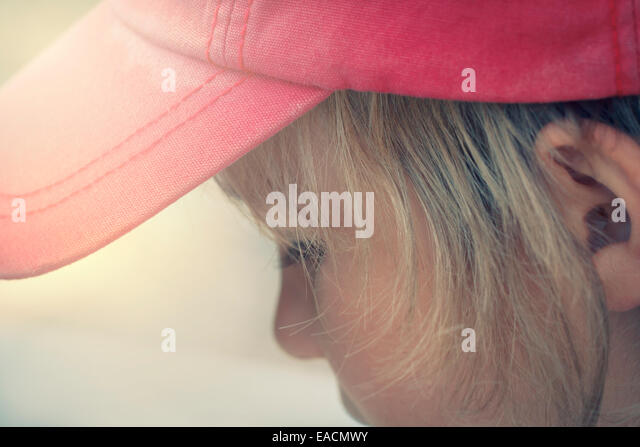 caucasian blond boy 6 years old wearing a baseball cap and looking down - Stock Image