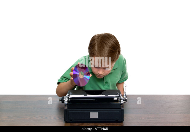 Young boy trying to work out where the DVD goes in this strange looking laptop Concept of youth and retro technology - Stock-Bilder