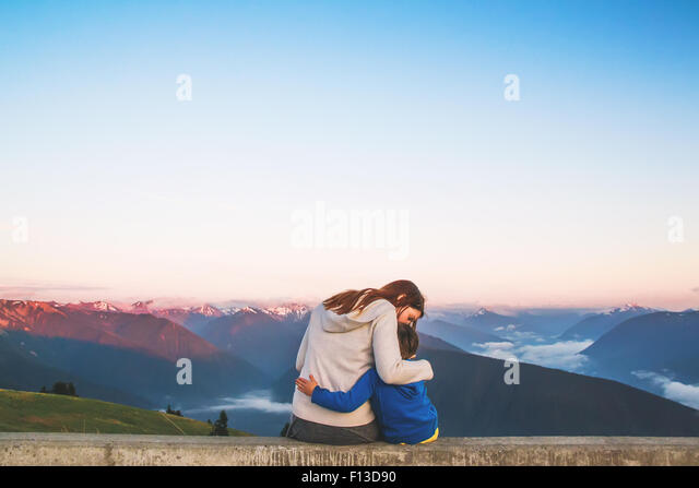 Rear view of woman sitting on a wall hugging her son - Stock Image