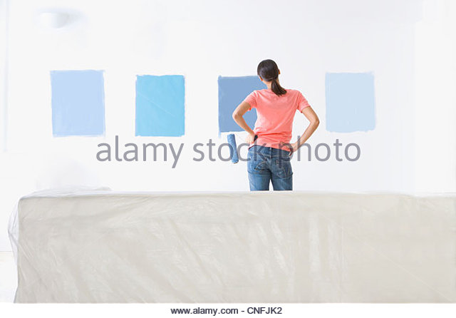Woman holding paint roller and examining blue paint samples on living room wall - Stock Image
