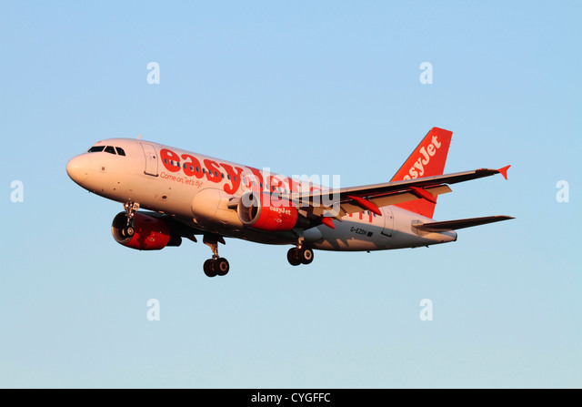 Cheap flights. Airbus A319 passenger jet belonging to low cost airline easyJet on approach at sunset - Stock Image