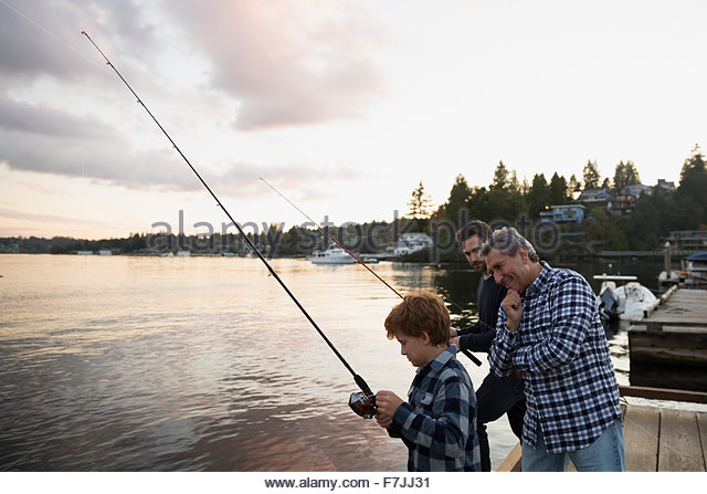 Multi-generation family fishing lake dock at sunset - Stock Image