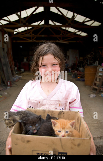 Young girl in rural Iowa, holding box of new kittens, Iowa, USA - Stock Image