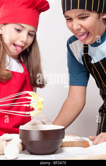 Boy with his sister looking with disgust at the raw mixture of cake - Stock Image