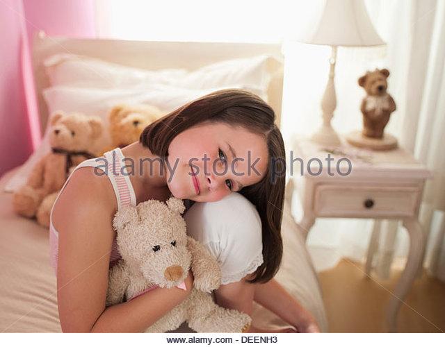 Girl hugging stuffed animal on bed - Stock-Bilder