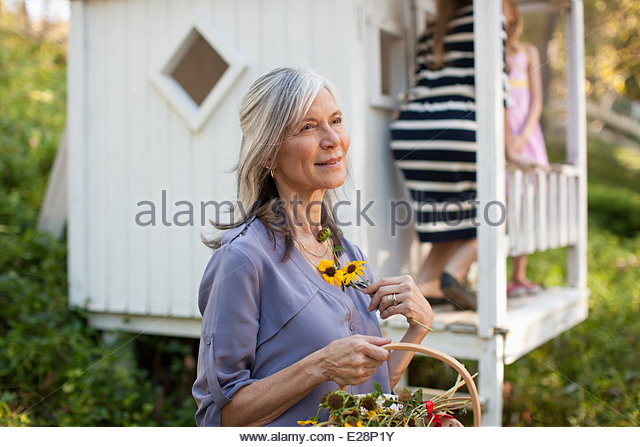 Older woman picking flowers outdoors - Stock Image