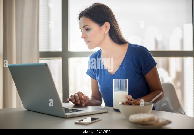 Young woman using laptop whilst having breakfast - Stock-Bilder
